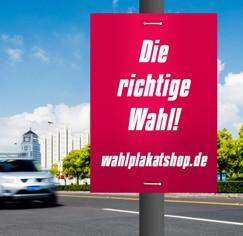 Wahlplakat aus Hohlkammermaterial an einer Straßenlaterne am Straßenrand